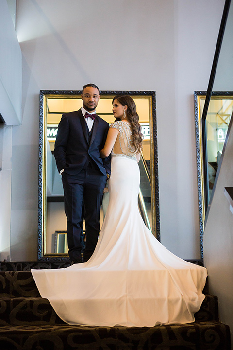 bride with a soft finger wave hair style with delicate makeup and gold earrings, the groom in a navy tuxedo with a black satin lapel and a purple bow tie at the top of the stairs