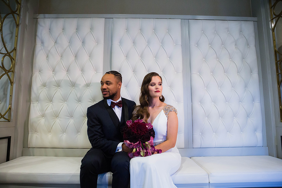bride in a satin white formfitting gown with a plunging neckline and a trumpet train skirt holding a bouquet of purple flowers the groom in a navy tuxedo with a black satin lapel and a purple bow tie sitting on the white regal couch