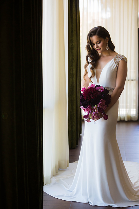 bride in a satin white formfitting gown with a plunging neckline and a trumpet train skirt holding a bouquet of purple flowers