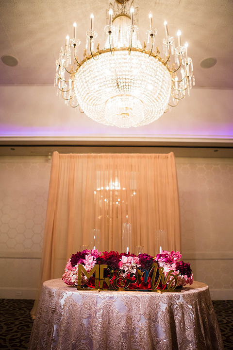 sweetheart table with rose gold linens and pink and purple flowers and gold Mr. and Mrs. lettering