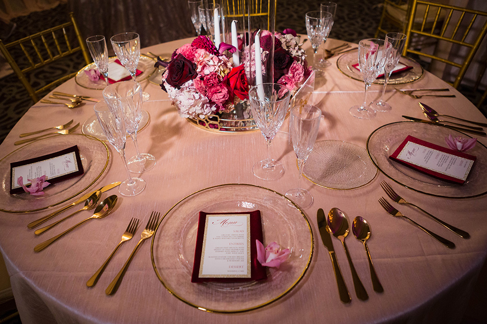 sweetheart table with rose gold linens and pink and purple flowers and gold Mr. and Mrs. lettering and gold flatware