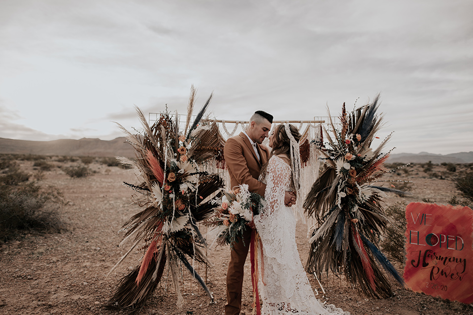 bride in a bohemian gown with long sleeves and lace detailing and the groom in a caramel suit with a brown long tie and a fun colored ceremony arch with bright colored pampas grass