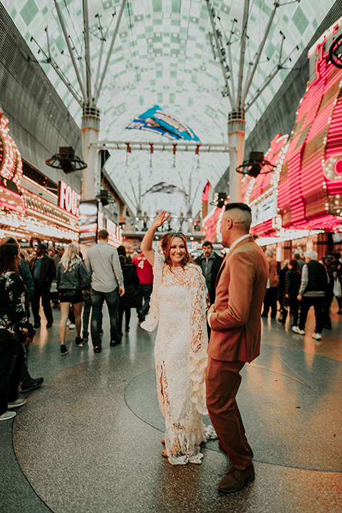 bride in a bohemian white gown with lace detailing and long sleeves and the groom in a caramel rust suit color with a brown long tie, smiling downtown