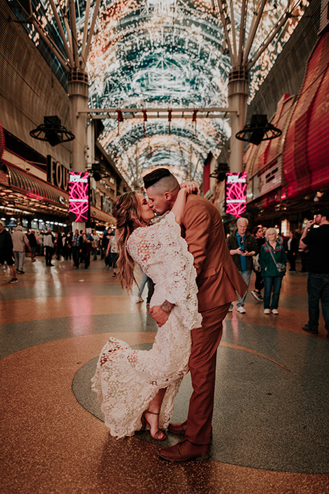 bride in a bohemian white gown with lace detailing and long sleeves and the groom in a caramel rust suit color with a brown long tie, kissing downtown