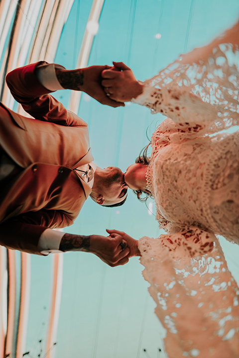 bride in a bohemian white gown with lace detailing and long sleeves and the groom in a caramel rust suit color with a brown long tie, kissing on freemont street