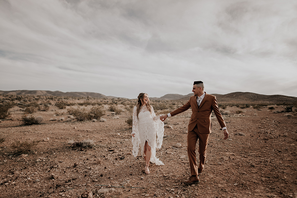 bride in a bohemian gown with long sleeves and lace detailing and the groom in a caramel suit with a brown long tie walking in the desert