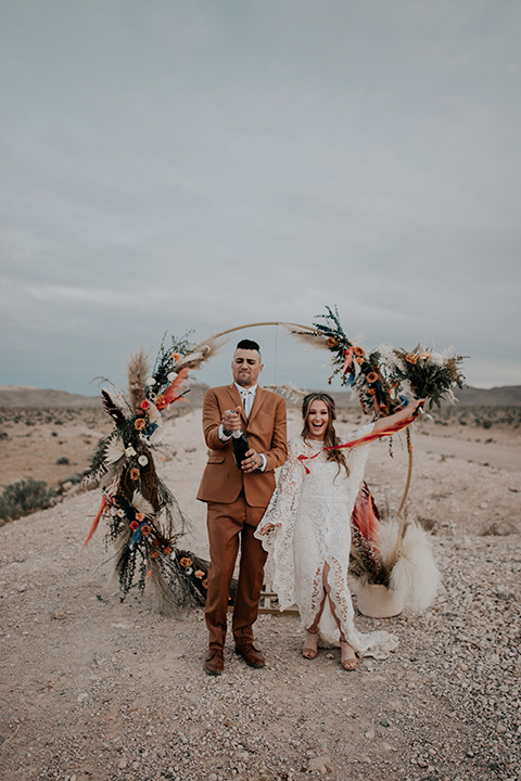 bride in a bohemian white gown with lace detailing and long sleeves and the groom in a caramel rust suit color with a brown long tie, opening champagne
