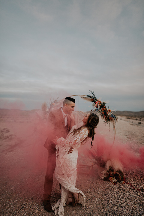 bride in a bohemian white gown with lace detailing and long sleeves and the groom in a caramel rust suit color with a brown long tie, they are dancing in with pink smoke around them