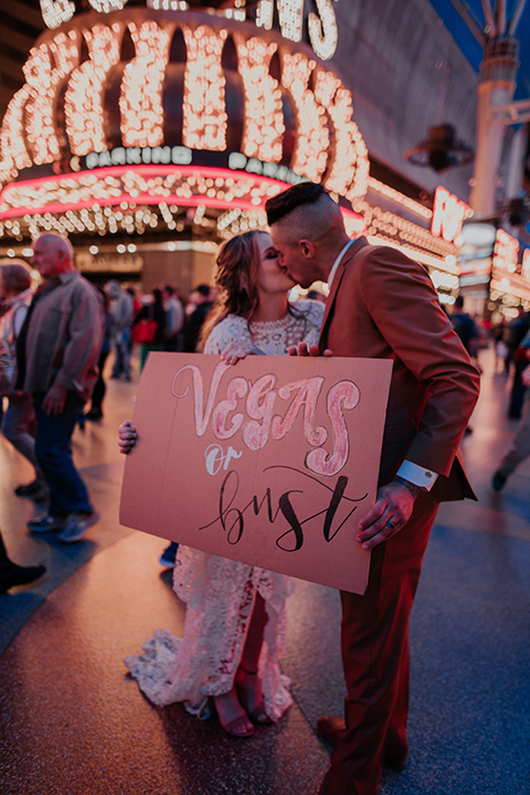 bride in a bohemian white gown with lace detailing and long sleeves and the groom in a caramel rust suit color with a brown long tie, dancing on freemont street