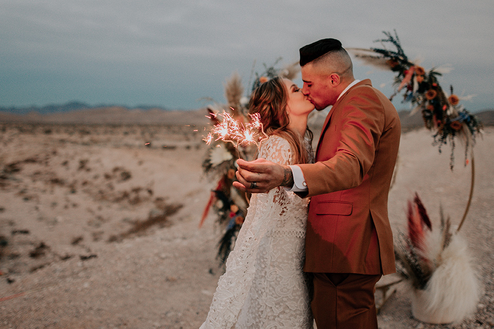 bride in a bohemian gown with long sleeves and lace detailing and the groom in a caramel suit with a brown long tie with sparklers kissing