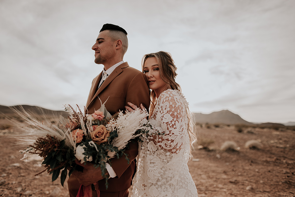 bride in a bohemian gown with long sleeves and lace detailing and the groom in a caramel suit with a brown long tie hugging
