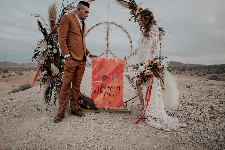 bride in a bohemian gown with long sleeves and lace detailing and the groom in a caramel suit with a brown long tie at ceremony