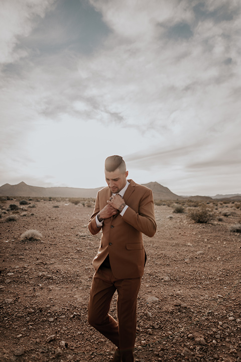 the groom in a caramel rust suit color with a brown long tie walking