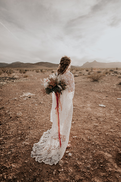 bride in a bohemian white gown with lace detailing and long sleeves