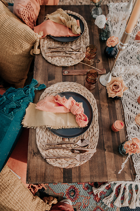 wooden table with tall candles and bohemian style table decor