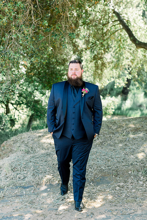 groom in a navy blue tuxedo with a black shirt