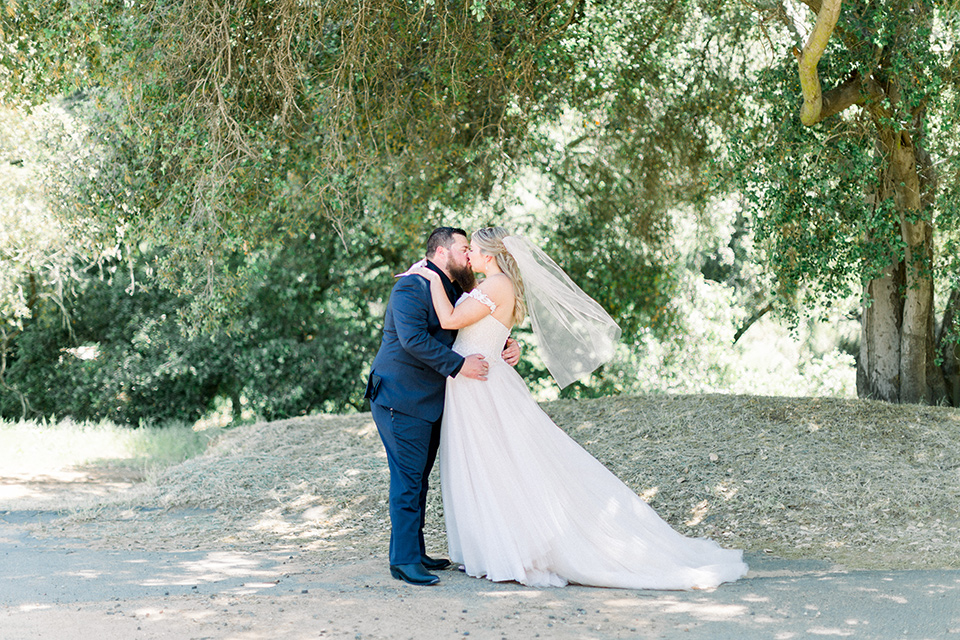 bride in a white ballgown with an off the shoulder detail looking out the window, groom in a navy blue tuxedo with a black shirt and bow tie