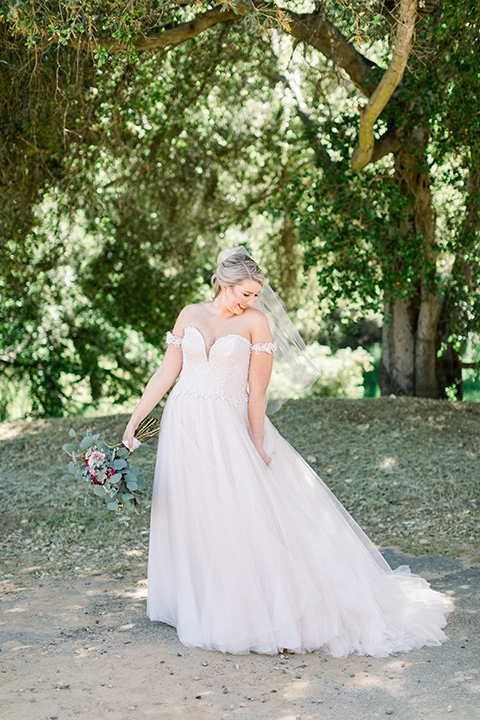 bride in a white ballgown with an off the shoulder detail looking out the window