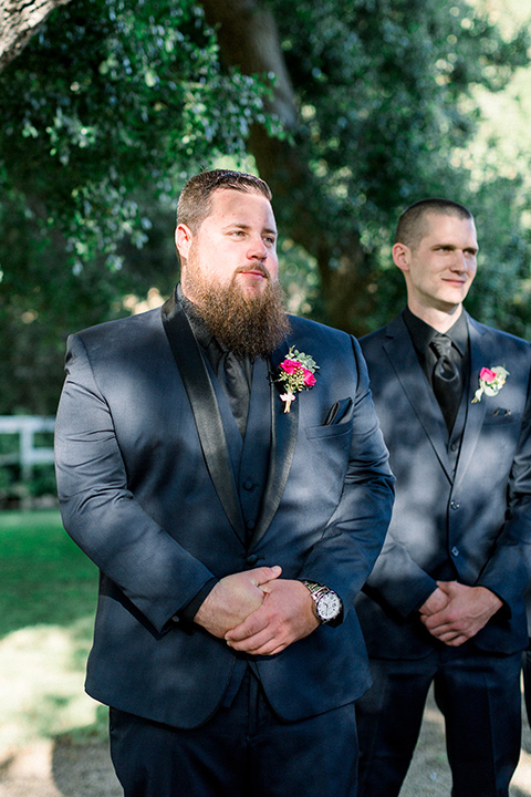 groom in a navy blue tuxedo with a black shirt and bow tie with his groomsmen at the ceremony