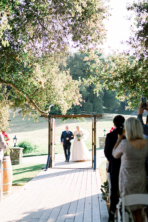 bride in a white ballgown with an off the shoulder detail walking down the aisle with father