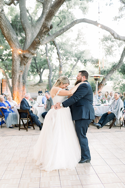 bride in a white ballgown with an off the shoulder detail and groom in a navy blue tuxedo with a black shirt and bow tie dancing