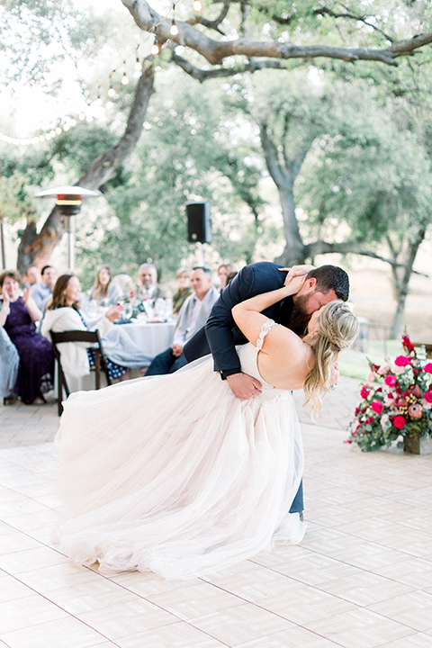bride in a white ballgown with an off the shoulder detail and the groom in a navy blue tuxedo with a black shirt and bow tie dipping his bride