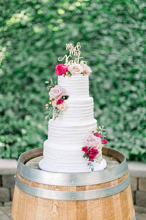 white cake with pink and red flowers on it
