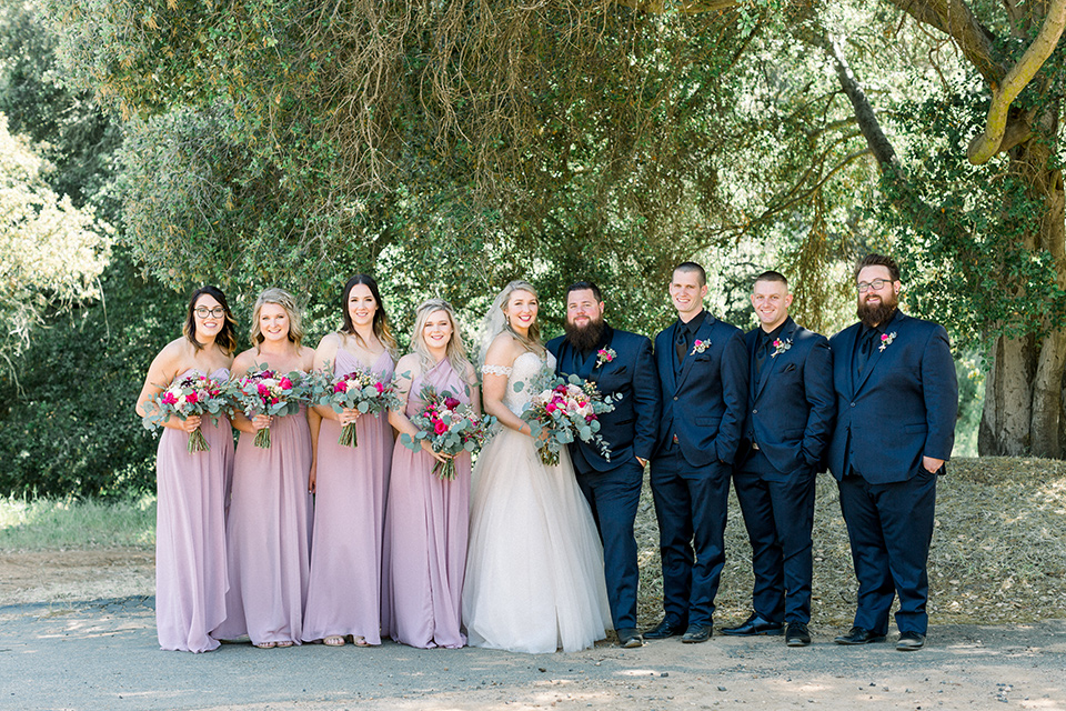 bride in a white ballgown with an off the shoulder detail looking out the window, groom in a navy blue tuxedo with a black shirt and bow tie, groomsmen in navy suits with florals ties and bridesmaids in pink long gowns