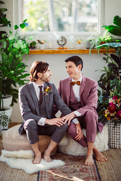 groom in a café brown suit and a brown long tie and the other groom in a rose pink suit with a gold velvet bow tie, outside at the ceremony
