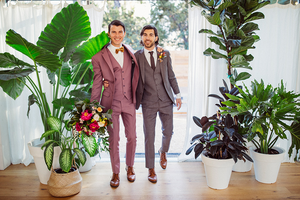 groom in a café brown suit and a brown long tie and the other groom in a rose pink suit with a gold velvet bow tie at ceremony
