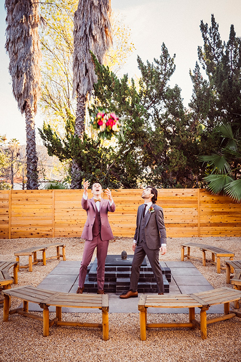 groom in a café brown suit and a brown long tie and the other groom in a rose pink suit with a gold velvet bow tie, outside at the reception