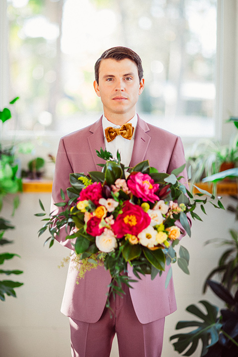 groom in a rose pink suit with a gold velvet bow tie
