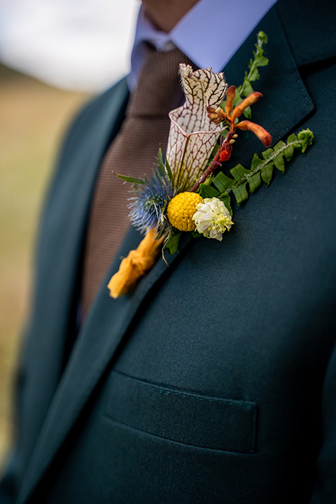 the groom in a dark green suit and brown long tie