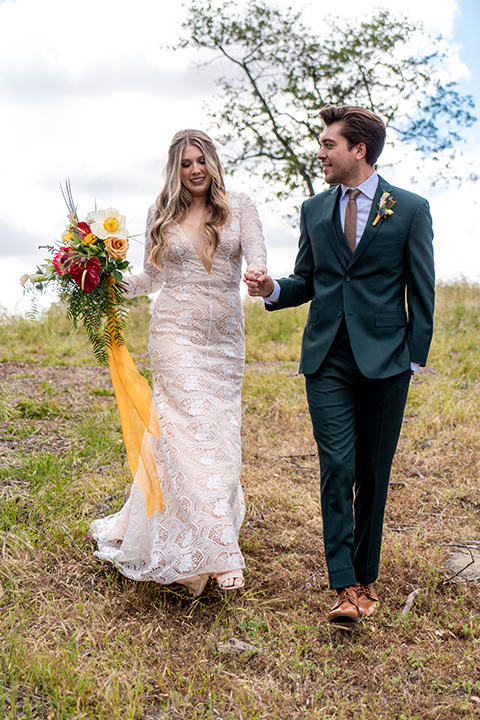 the groom in a dark green suit and brown long tie and bride in a lace gown with long sleeves