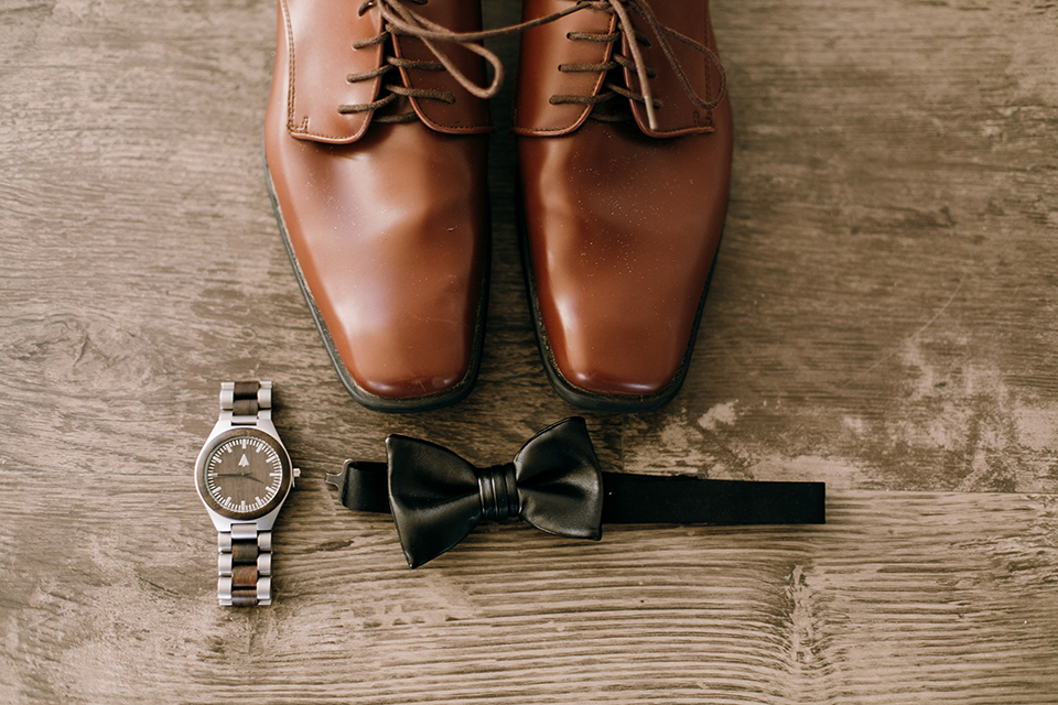 brown shoes with a black bow tie on it