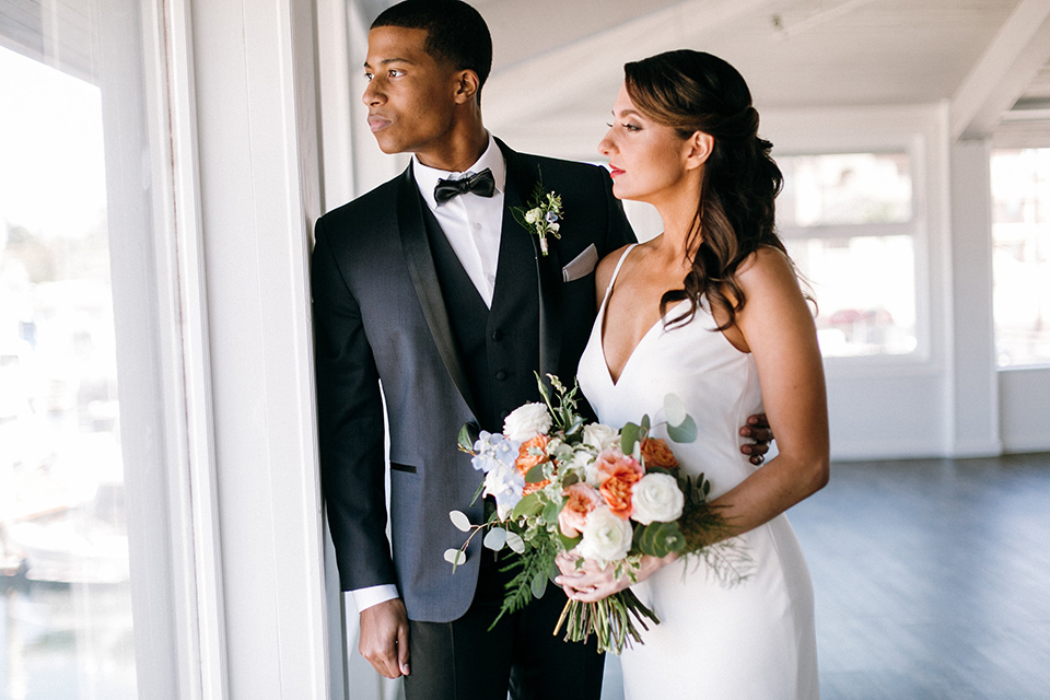 bride in a lace white gown with a long veil and the groom in a navy shawl lapel tuxedo with black bow ties
