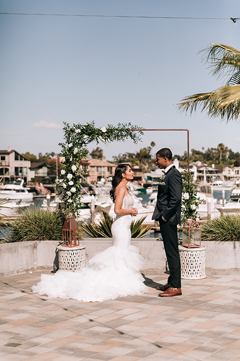 bride in a lace white gown with a long veil and the groom in a navy shawl lapel tuxedo with black bow ties, and the bridesmaid in a silver long gown and the groomsmen in a navy shawl lapel tuxedo with a black bow tie on the beach