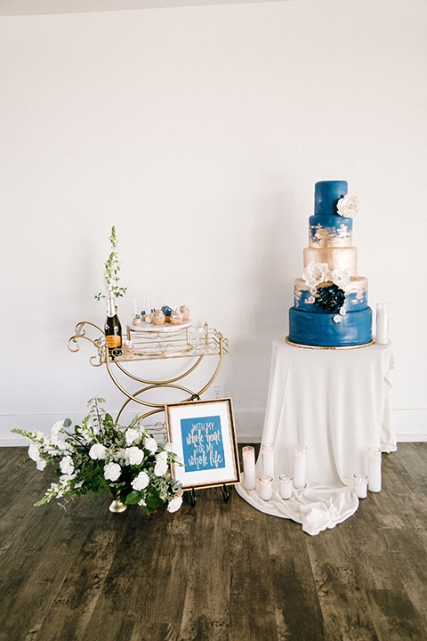 white and blue cake with white table linens and gold decor