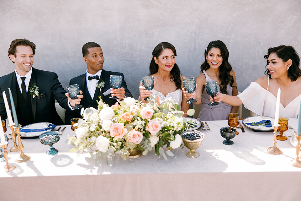bride in a lace white gown with a long veil and the groom in a navy shawl lapel tuxedo with black bow ties, and the bridesmaid in a silver long gown and the groomsmen in a navy shawl lapel tuxedo with a black bow tie