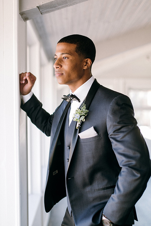 the groom in a navy shawl lapel tuxedo with black bow ties