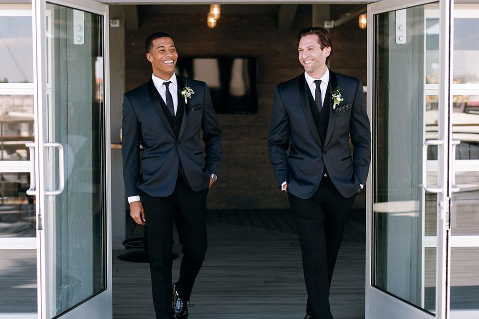 groom and groomsmen in a navy shawl lapel tuxedos with black bow ties
