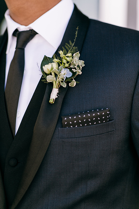 groom in a navy shawl lapel tuxedo with black bow ties and white pocketsquare