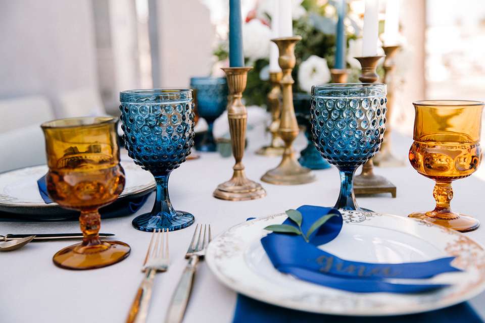 blue and orange décor on a table with white linens and gold flatware