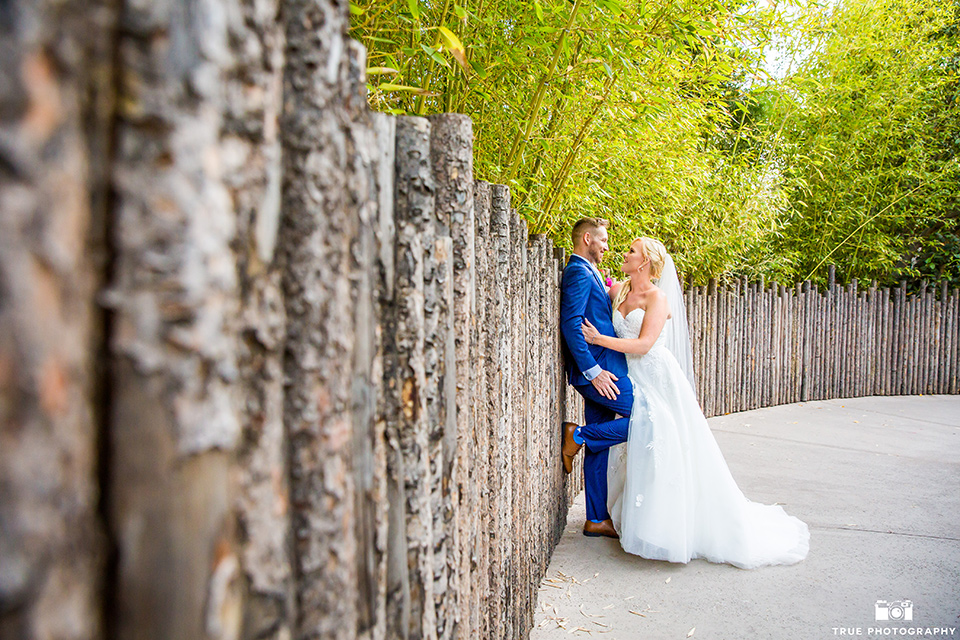 bride in a lace gown with a strapless neckline, groom in a cobalt blue suit and long tie