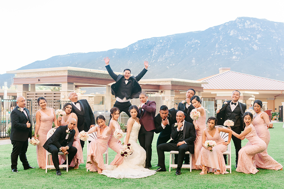 bride in a lace formfitting gown and a high neckline and the groom in a burgundy tuxedo with a black bow tie, and the bridesmaids in a rose blush gowns and the groomsmen in a black tuxedo with a black bow tie