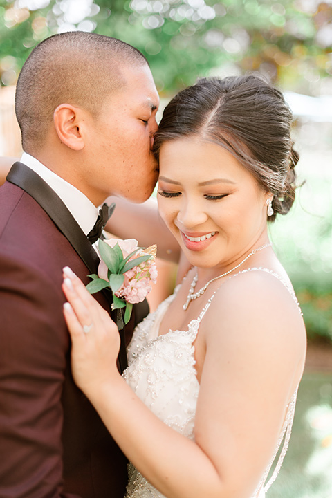 bride in a lace formfitting gown and a high neckline and the groom in a burgundy tuxedo with a black bow tie close together