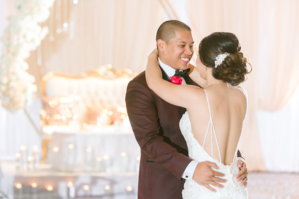 bride in a lace formfitting gown and a high neckline and the groom in a burgundy tuxedo with a black bow tie dancing at the reception