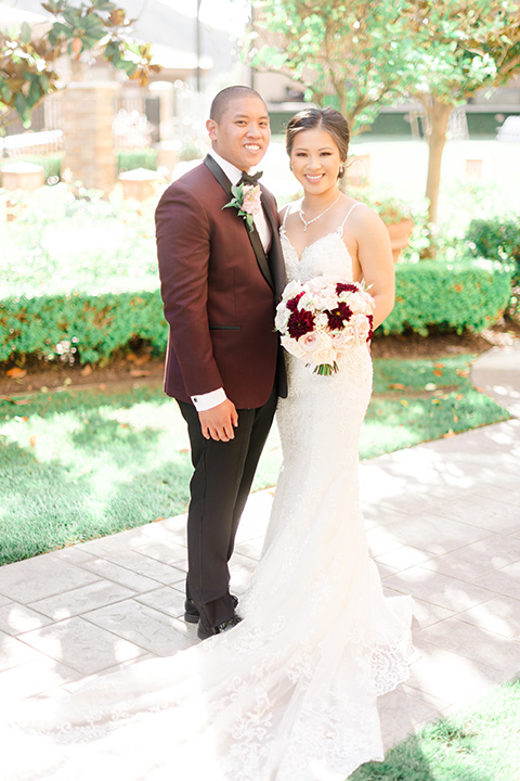 bride in a lace formfitting gown and a high neckline and the groom in a burgundy tuxedo with a black bow tie smiling