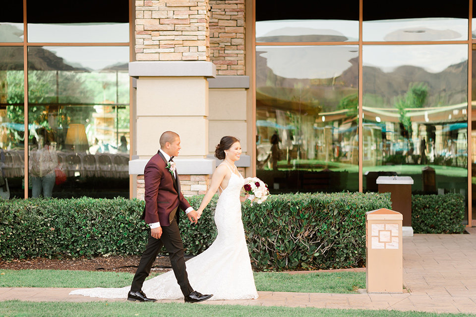 bride in a lace formfitting gown and a high neckline and the groom in a burgundy tuxedo with a black bow tie walking