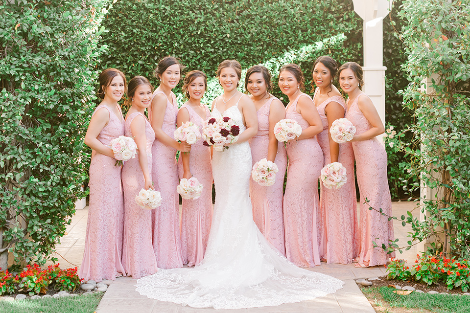 bride in a lace formfitting gown and a high neckline and the bridesmaids in a rose blush gowns